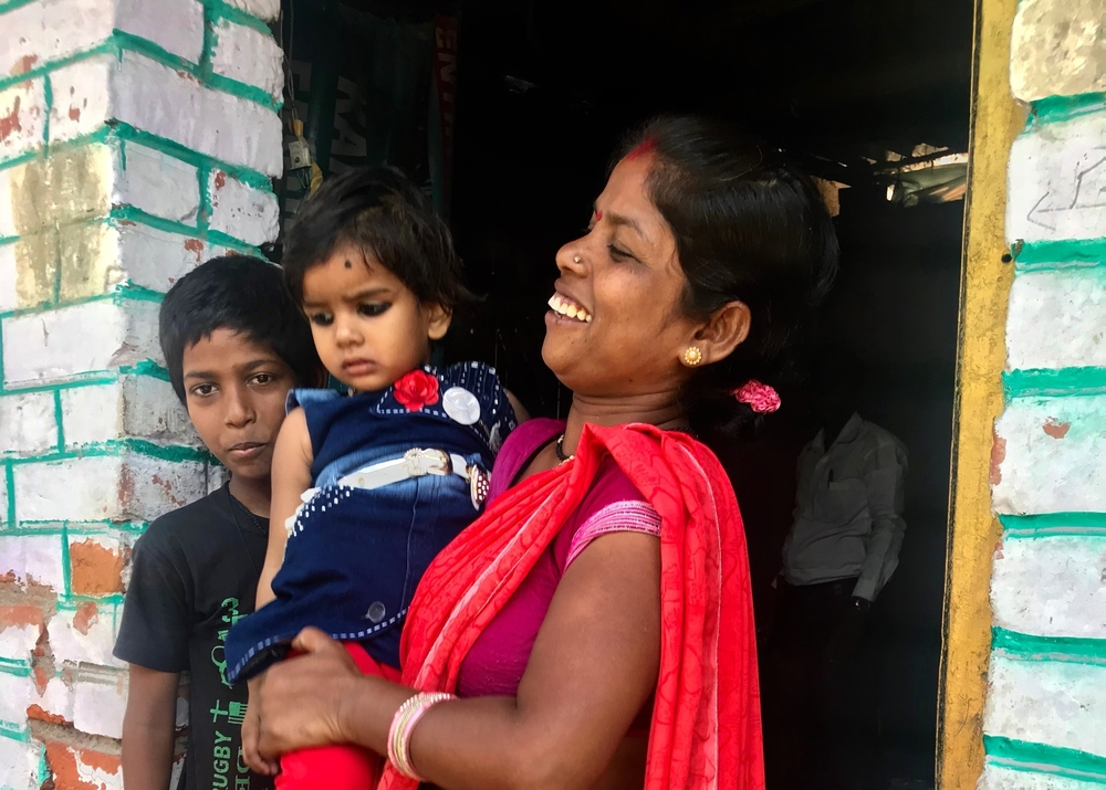 Ranjana, who was featured in our original story, with her children outside her house in Kanpur.