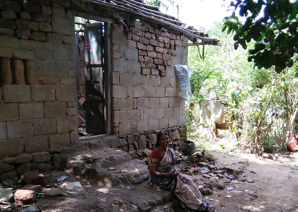 Devaki, sitting in front of her home, which was badly damaged during the flood. Photo by SaveAGram