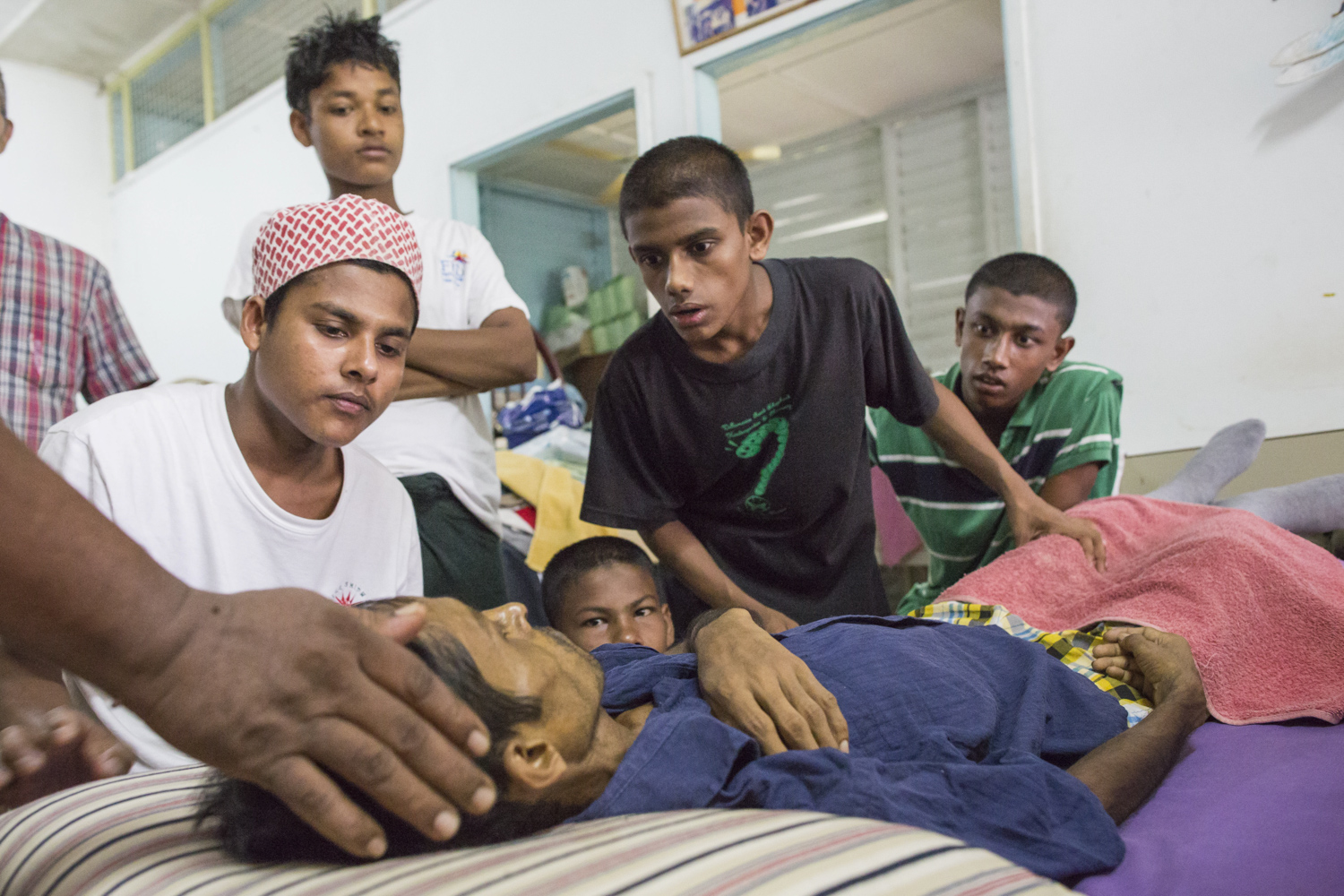 Alex and the Rohingya boys watching over Rashedul as his blood pressure drops dangerously low. Rashedul was terminally ill with liver cancer, and needed palliative care.
