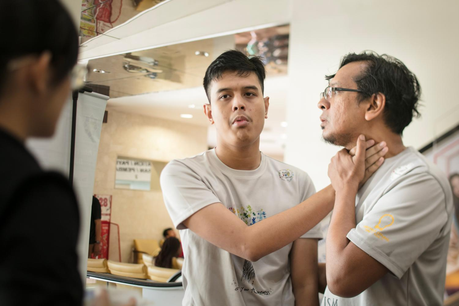 When talking to customers, Adli helps Luqman regulate the volume of his voice by letting him feel the vibration from his vocal chords.